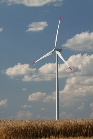 Wind power generator in a wheat field, close-up. Vertical shot with blue sky and clouds in the background.