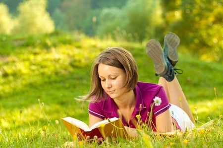 Beatiful woman laying on the ground in a park and enjoying a book. Horizontal shot. Standard-Bild
