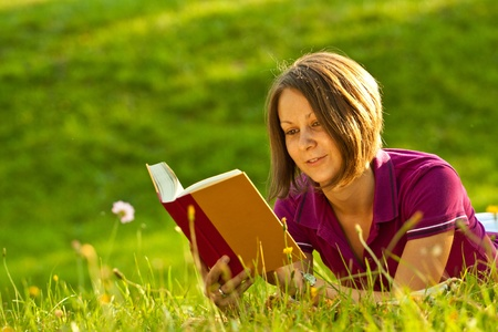 Beatiful woman reading a book in the park