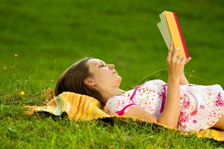 Beautiful woman laying on the ground in a park and reading a book. Horizontal shot with copyspace. Standard-Bild