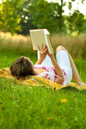 Hermosa mujer tumbada en el suelo en un parque y leer un libro. Tiro horizontal con copyspace.