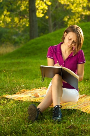 Beatiful woman sitting on the ground in a park and writing in her diary. Vertical shot with copyspace. Stock Photo - 10516420