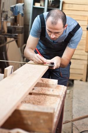 woodworker: Man measuring a beech wood plank