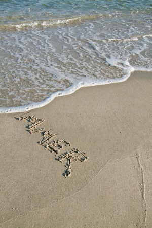 end of the day: Summer, written on the sand and washed away. Simbolizes the end of the summer. Stock Photo
