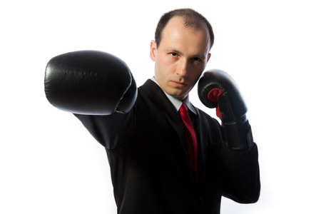 Businessman with a tie and boxing gloves punching, horizontal shot isolated on white photo
