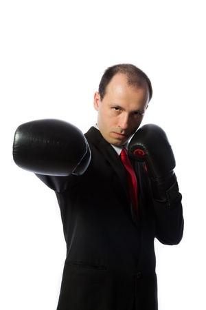 Businessman with a tie and boxing gloves punching, vertical shot isolated on white. photo