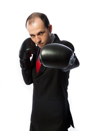 Businessman with boxing gloves in fighting stance punching Standard-Bild