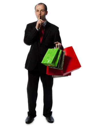 Businessman with shopping bags and making quiet sign with hand, vertical shot isolated on white. Stock Photo - 13293723
