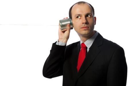 tin cans: Man luisteren door middel van een oldschool blik telefoon, horizontaal schot op wit wordt geïsoleerd