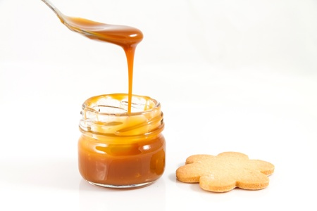 caramel: Pouring caramel in a small jar with a spoon with a cookie next to it, horizontal shot