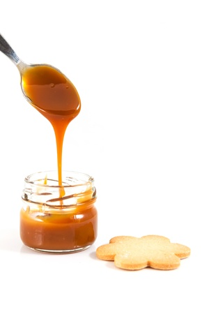 caramel: Pouring caramel in a small jar with a spoon with a cookie next to it, vertical shot Stock Photo