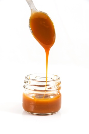 Pouring caramel in a small jar with a spoon photo