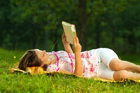 Beautiful young brunette reading on a meadow in the park photo