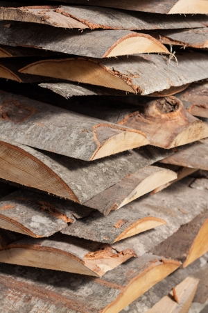 Pile of beech planks with bark photo