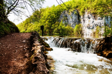 Beaten track near a forest lake and waterfall in Plitvice Lakes National Park, Croatia photo