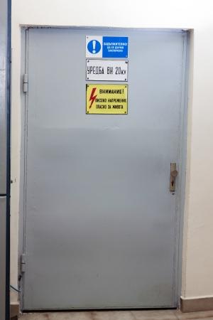 security door: Industrial door with high voltage warning sign