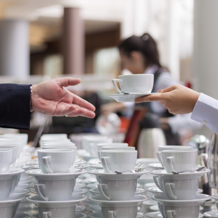 Hand offering a coffee with many coffee cups