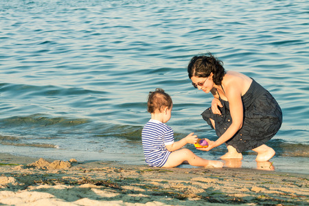 Mother and toddler playing on the beach