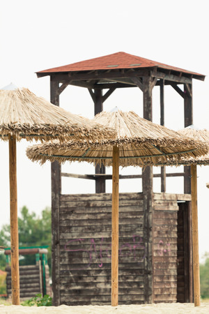 watchtower: Straw umbrellas and lifeguard watchtower at a beach. Photo with untraditional color rendering for artisctic look