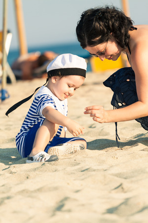 Sweet smiling toddler dressed as a sailor sitting on a beach and exploring the sand and shells with his mother. Photo with untraditional color rendering for artistic look photo