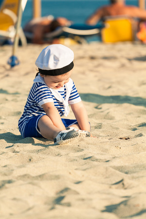 Sweet smiling toddler dressed as a sailor sitting on a beach and playing with the sand. Photo with untraditional color rendering for artistic look photo