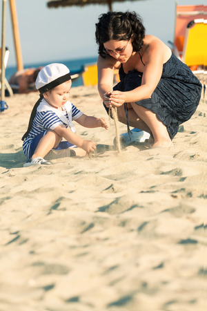 Sweet toddler dressed as a sailor sitting on a beach and playing with the sand with his mother. Photo with untraditional color rendering for artistic look photo