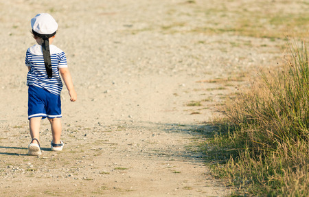 Sweet toddler dressed as a sailor walking with determination on a gravel road. Photo with untraditional color rendering for artistic look Standard-Bild