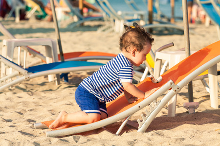 Toddler dressed as a sailor climbing on a tilted sunbed on a beach. Photo with untraditional color rendering for artistic look