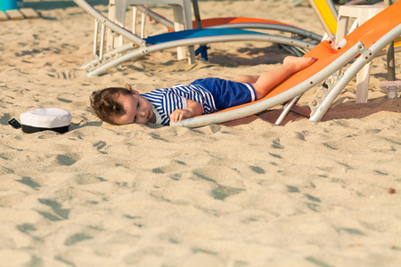 Toddler dressed as a sailor lying from a top of a sunbed on a beach and looking as he is drunk with his hat near him. Photo with untraditional color rendering for artistic look Standard-Bild