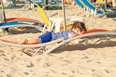 Toddler dressed as a sailor lying on a sunbed on a beach. Photo with untraditional color rendering for artistic look