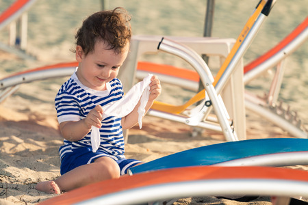 Toddler dressed as a sailor playing with his clothes near sunbeds on a beach. Photo with untraditional color rendering for artistic look Standard-Bild