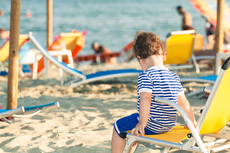 Toddler dressed as a sailor sitting on a beach chair with other people in defocussed background. Photo with untraditional color rendering for artistic look