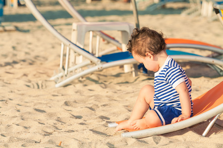 Toddler dressed as a sailor sitting on a tilted sunbed and exploring the sand on a beach. Photo with untraditional color rendering for artistic look Standard-Bild