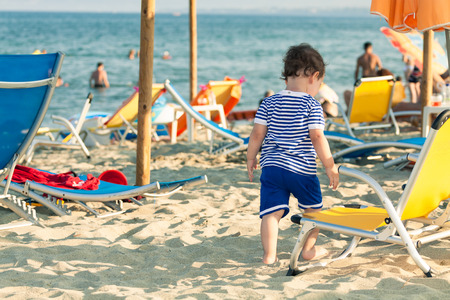 Toddler dressed as a sailor standing near a beach chair with other people in defocussed background. Photo with untraditional color rendering for artistic look Standard-Bild