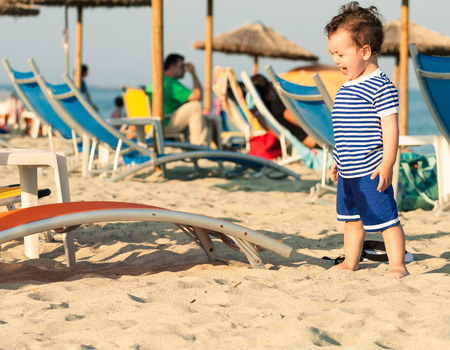 Toddler dressed as a sailor standing on a beach and crying with other people in defocussed background. Photo with untraditional color rendering for artistic look Stock Photo
