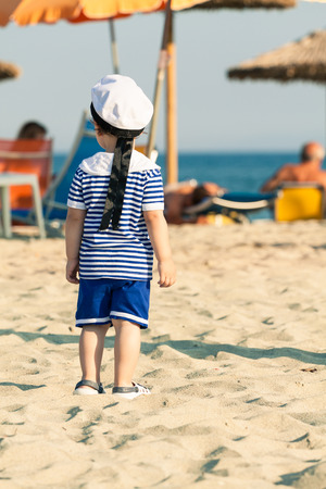 Toddler dressed as a sailor standing on a beach and looking around