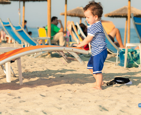 Toddler dressed as a sailor standing on a beach and playing with sunbed with other people in defocussed background. Photo with untraditional color rendering for artistic look