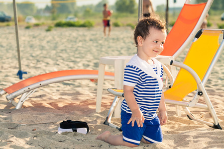 Toddler dressed as a sailor standing on his knees on a beach and giving a playful look. Photo with untraditional color rendering for artistic look Standard-Bild