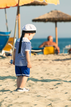 Toddler dressed as a sailor walking on a beach. Photo with untraditional color rendering for artistic look