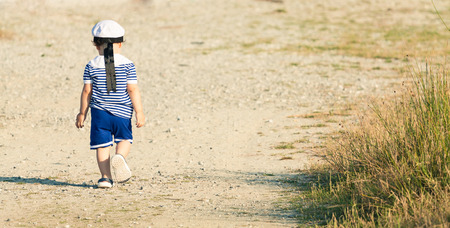 Toddler dressed as a sailor walking with determination on a gravel road. Panoramic photo with untraditional color rendering for artistic look