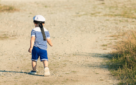 Toddler dressed as a sailor walking with determination on a gravel road. Photo with untraditional color rendering for artistic look