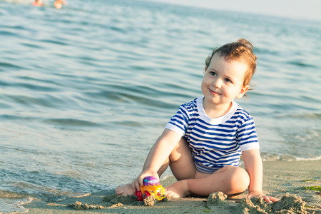 Toddler with sailor shirt playing with a car at the edge of the water on a beach. Photo with untraditional color rendering for artistic look