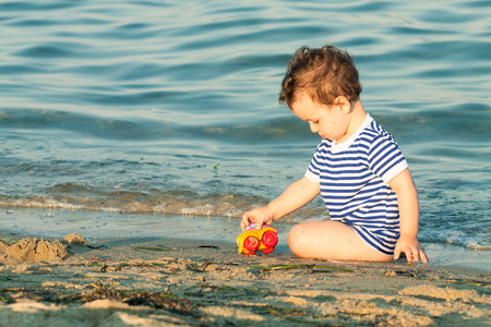 Toddler with sailor shirt sitting and playing at the edge of the waves on a beach. Photo with untraditional color rendering for artistic look