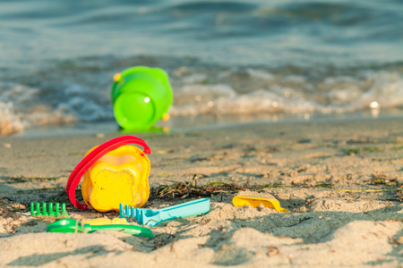 Toy buckets and other toys on a beach near the edge of the waves