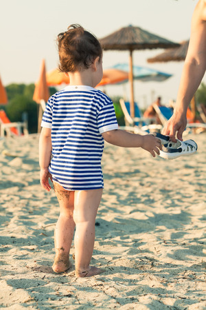 Woman hand giving flip flops to a toddler with sailor shirt on a beach. Photo with untraditional color rendering for artistic look Standard-Bild
