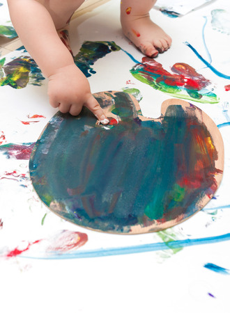 Toddler touching paints on a palette with finger