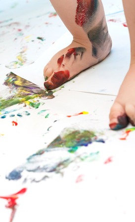 Close up of toddler's feet covered with paint on white paper sheets with colorful paintings Standard-Bild