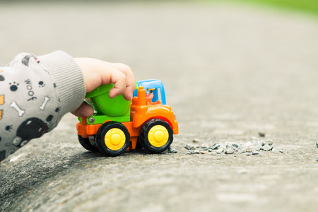Close up of a boy's hand playing with a toy truck