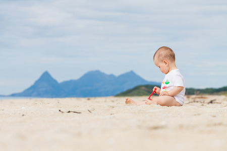 Baby playing on the beach with mountains in the background