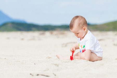 Adorable baby exploring the sand on the beach with a toy shovel with mountains in the background Standard-Bild